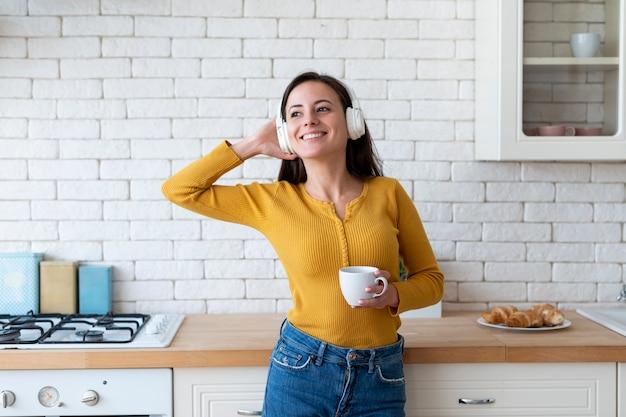Mujer escuchando música en la cocina Foto gratis