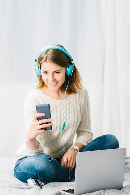 Mujer escuchando música y usando teléfono inteligente Foto Premium