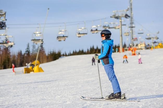 Mujer esquiadora esquiando cuesta abajo en la estación de esquí contra el remonte Foto Premium