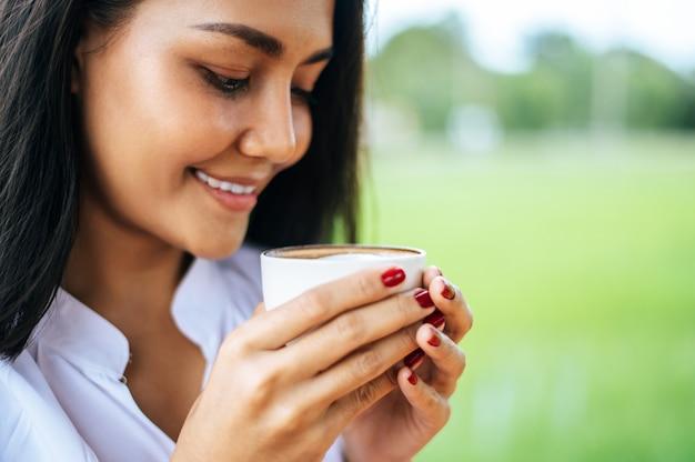 Mujer estaba felizmente tomando café en el prado Foto gratis