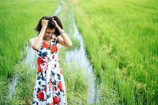 La mujer estaba tensa y la mano sostenía su cabello en el prado. Foto gratis