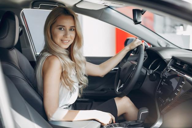 Mujer con estilo y elegante en un salón del automóvil Foto gratis
