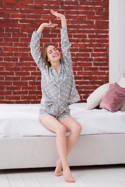 Mujer estirando los brazos después de despertarse Foto gratis