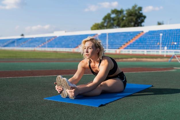Mujer estirando sobre estera en el estadio Foto gratis