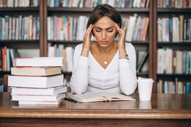 Mujer estudiante estudiando en la biblioteca y tomando café Foto gratis