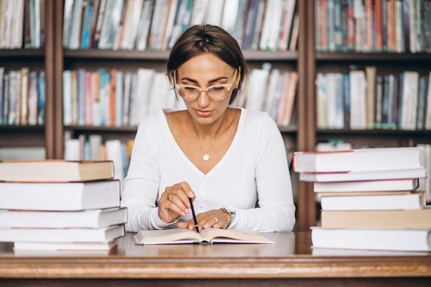 Mujer estudiante estudiando en la biblioteca Foto gratis