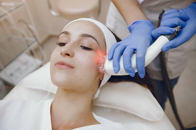 Mujer en estudio de cosmetología en depilación láser Foto gratis