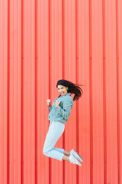 Mujer exitosa saltando delante de fondo texturado metalizado Foto gratis
