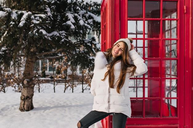 Mujer fascinante con el pelo largo de pie cerca de la cabina de teléfono roja y sonriendo Foto gratis
