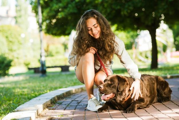 Mujer feliz acariciando a su perro en el parque Foto gratis