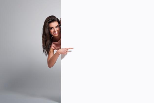 Mujer feliz apuntando al espacio de la copia en la pizarra Foto gratis