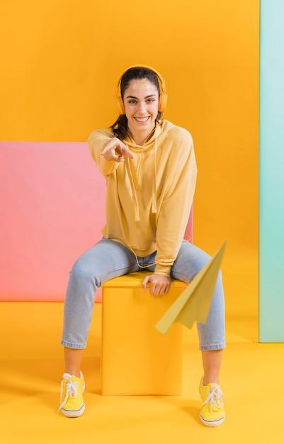 Mujer feliz con un avioncito de papel Foto gratis