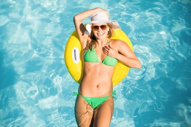 Mujer feliz en bikini verde flotando en el tubo inflable en la piscina Foto Premium