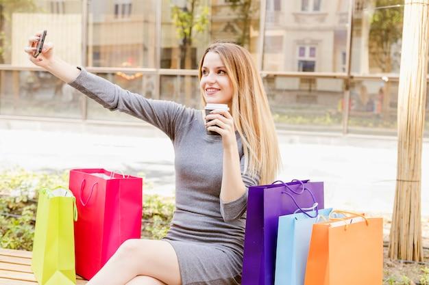 Mujer feliz con bolsas de compras multicolores tomando selfie en teléfono móvil Foto gratis
