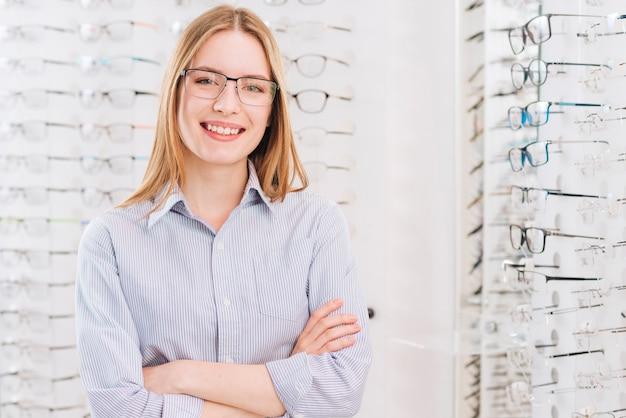 Mujer feliz buscando gafas nuevas en óptico Foto gratis