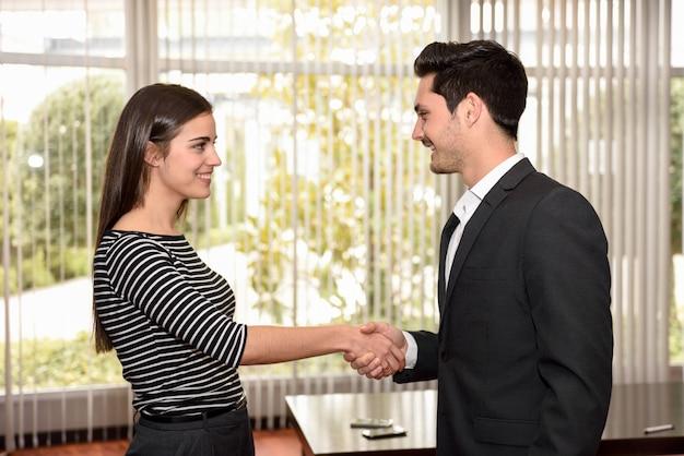 Mujer feliz dando la mano a su empleador después de una entrevista de trabajo Foto gratis