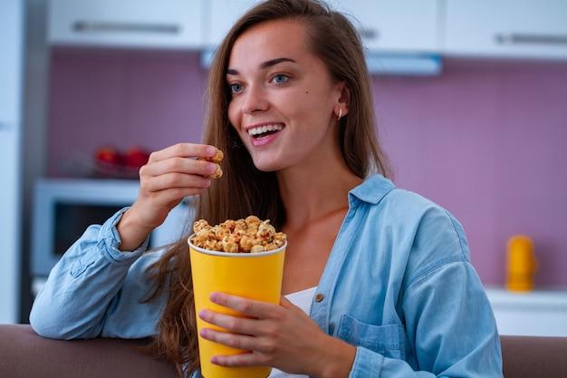 Mujer feliz descansando, riendo y comiendo crujientes palomitas de caramelo durante ver películas de comedia en casa. película de palomitas de maíz Foto Premium