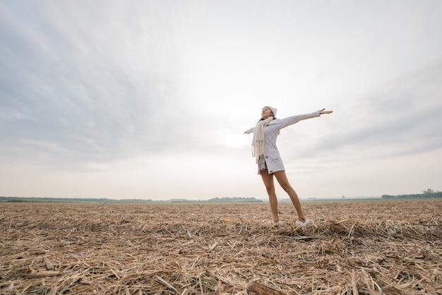 Mujer feliz disfrutando de la naturaleza idílica, celebrando la libertad y levantando los brazos. Foto gratis