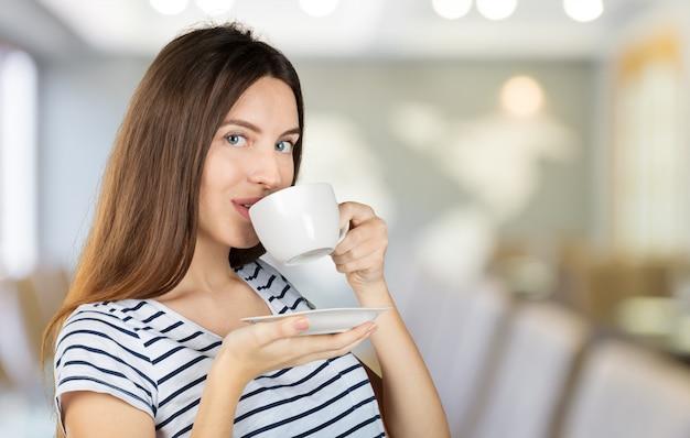 Mujer feliz disfrutando de una taza de té o café caliente para el desayuno Foto Premium