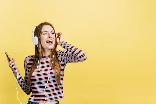 Mujer feliz escuchando música Foto gratis