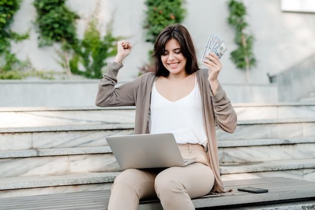 Mujer feliz gana dinero en la computadora portátil al aire libre Foto Premium
