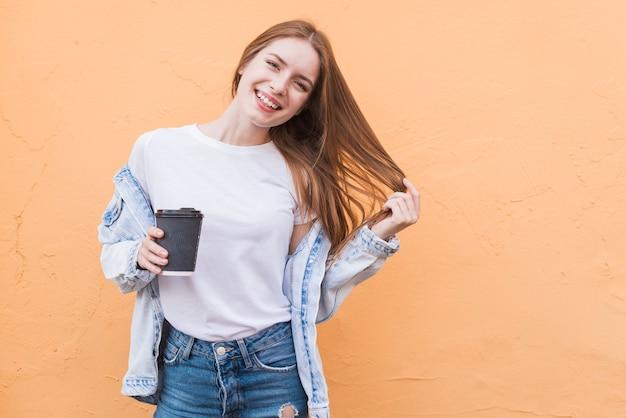 Mujer feliz hermosa que presenta cerca de fondo beige con sostener la taza disponible Foto gratis