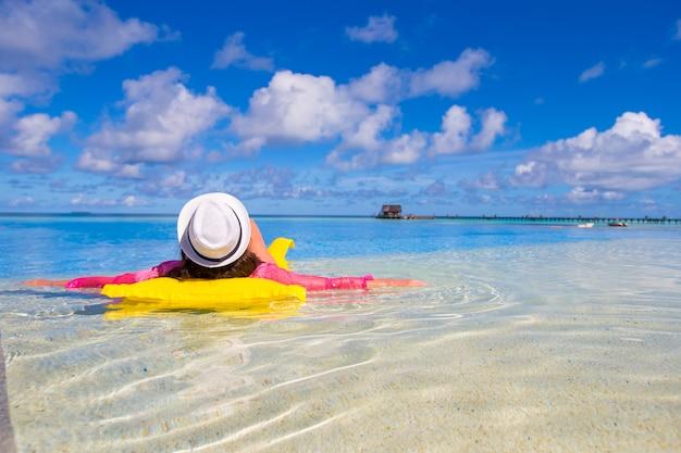 Mujer feliz joven que se relaja con el colchón de aire en piscina Foto Premium
