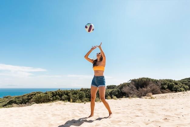 Mujer feliz jugando con la pelota en la playa Foto gratis