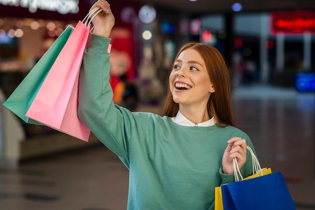 Mujer feliz levantando bolsas de compras Foto gratis