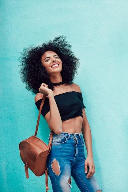 Mujer feliz mezclada con pelo afro parado en la calle Foto Premium
