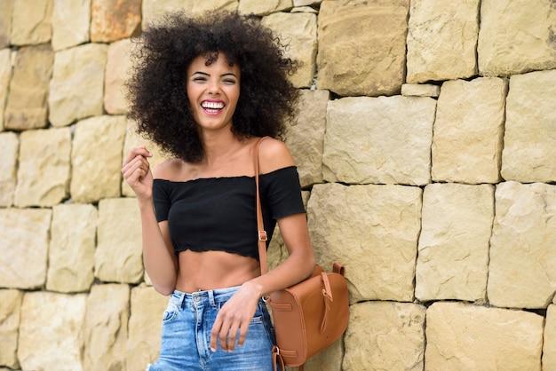 Mujer feliz mezclada con pelo afro riendo al aire libre Foto Premium