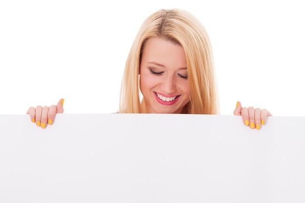 Mujer feliz mirando cartelera vacía Foto gratis