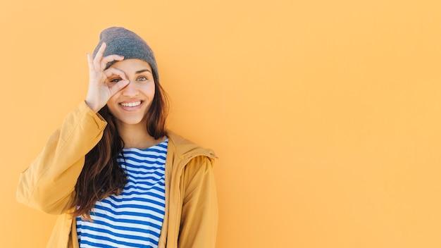 Mujer feliz mirando a través de la mano con sombrero hecho punto binocular Foto gratis