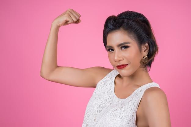 Mujer feliz de la moda que muestra su músculo bien sano Foto gratis