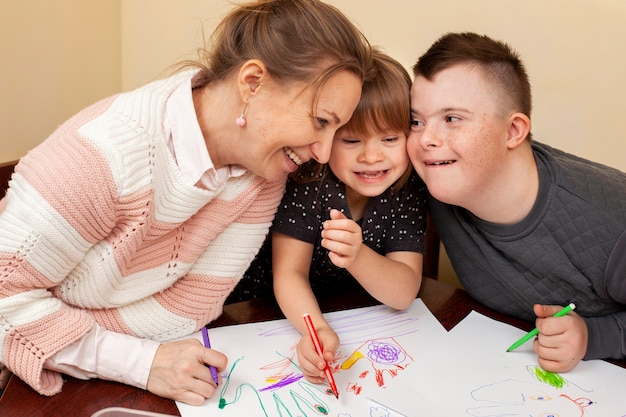 Mujer feliz con niños con síndrome de down Foto gratis