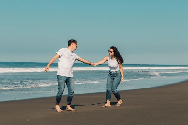 Mujer feliz que quiere que el hombre siga al agua en la playa Foto gratis