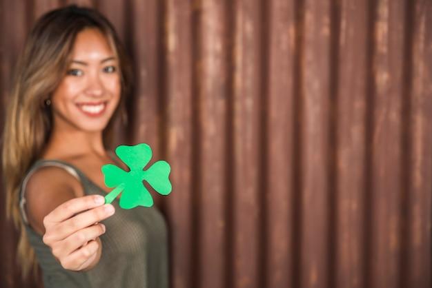 Mujer feliz que sostiene el trébol de papel verde Foto gratis