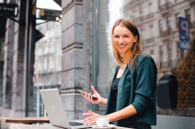 Mujer feliz que trabaja en una computadora portátil al aire libre Foto Premium