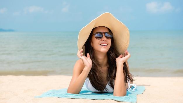 Mujer feliz relajante en la playa en verano Foto Premium