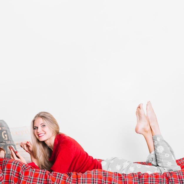 Mujer feliz con smartphone acostado en cama Foto gratis