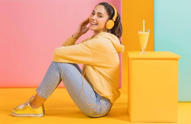 Mujer feliz con un vaso de jugo Foto gratis
