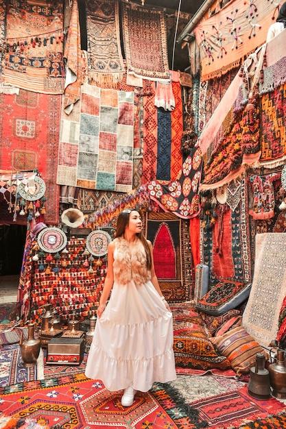Mujer feliz viaje con increíbles alfombras de colores en la tienda de alfombras locales, goreme. capadocia turquía Foto Premium