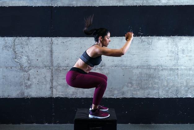 Mujer de fitness de construcción muscular fuerte en ropa deportiva haciendo entrenamiento de salto en el gimnasio Foto gratis