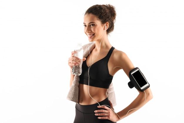 Mujer de fitness morena rizada feliz escuchando música y mirando a otro lado Foto gratis