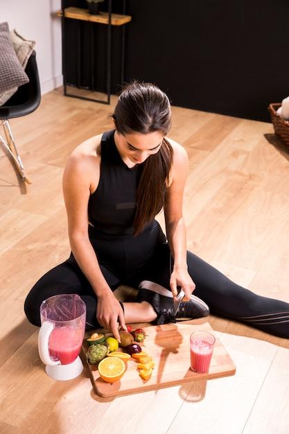 Mujer fitness preparando un zumo desintoxicante Foto gratis