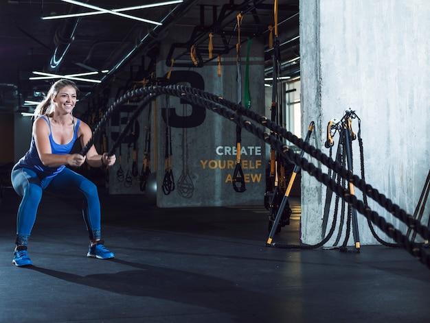 Mujer en forma haciendo ejercicio con cuerdas de batalla en el gimnasio Foto gratis