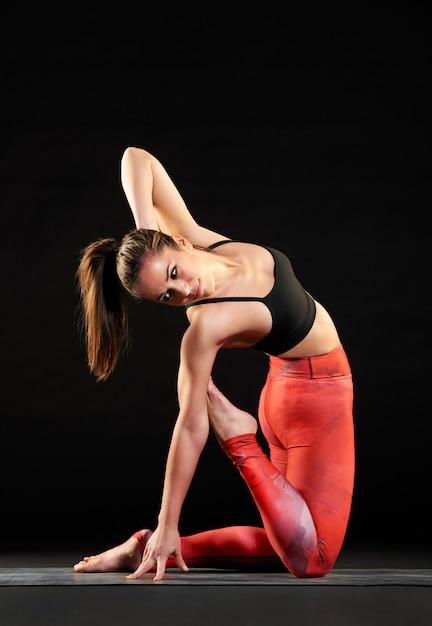 Mujer en forma muscular haciendo una variación de pose de camello Foto Premium