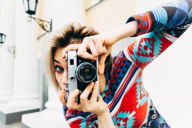 Mujer fotografiada cámara retro en la ciudad Foto Premium