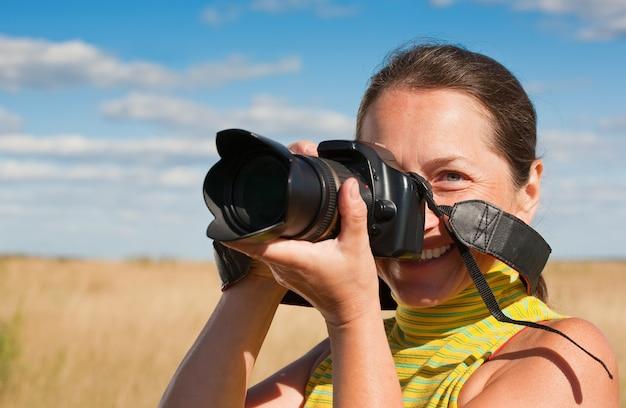 Mujer fotógrafo con cámara Foto gratis