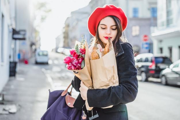 Mujer francesa con baguettes en la calle en beret Foto gratis